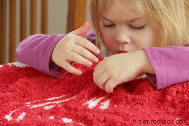 Child playing with a salt tray to address bilateral coordination and visual motor integration skills.