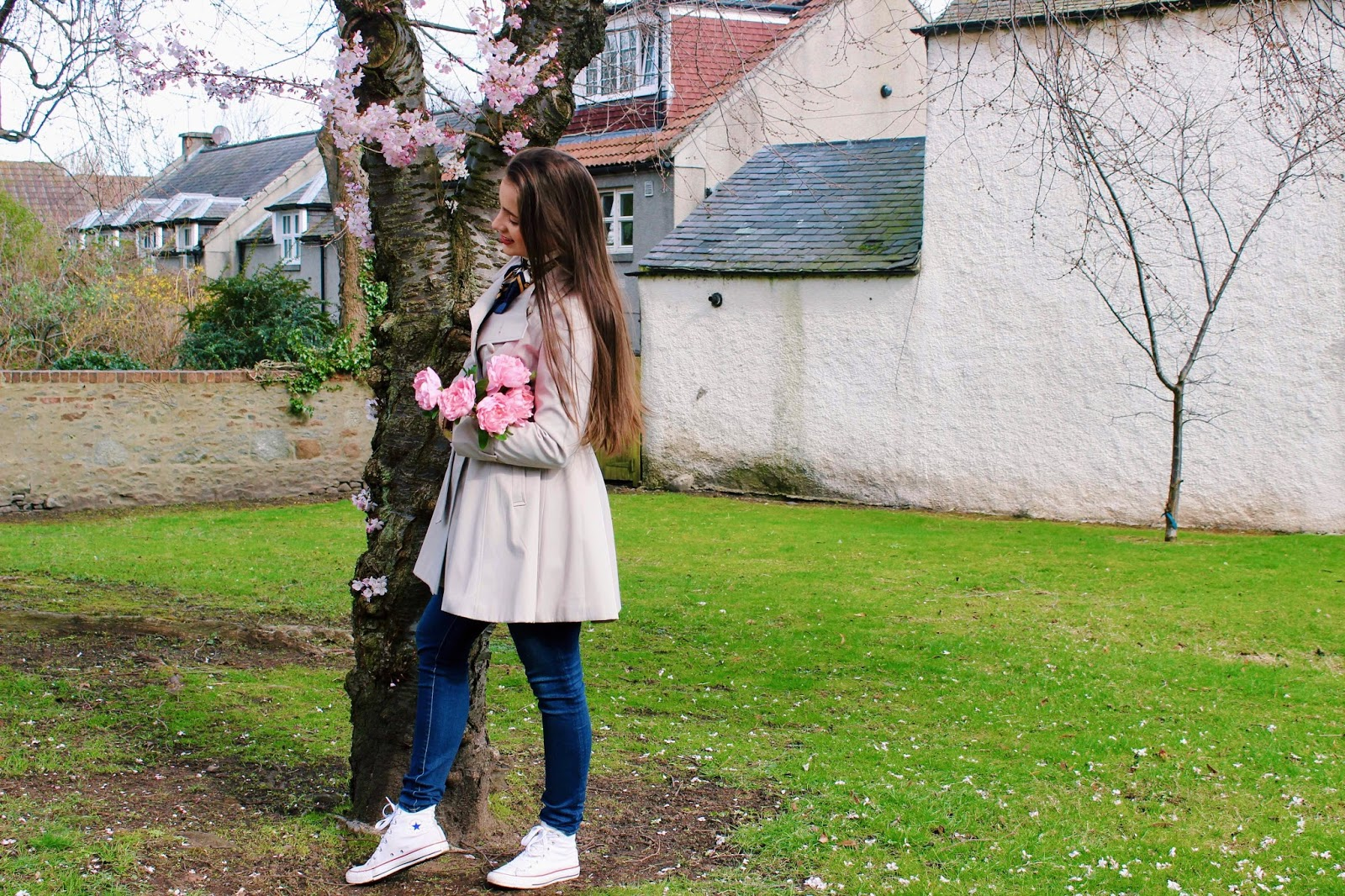 Girl under cherry blossom tree with flowers