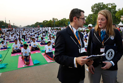Guinness World Records officials Marco Frigatta, second right, talks to his colleague Victoria Julie Tweedy during Yoga Day at Rajpath