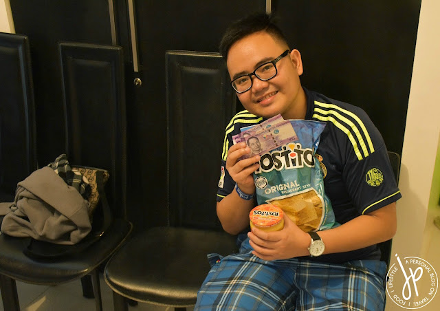 man in glasses holding money, bag of chips and a jar of dip