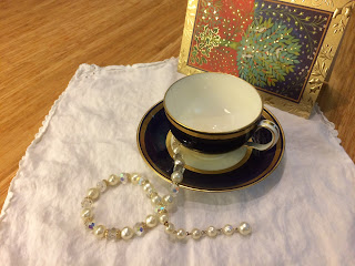 Tea cup on scalloped white napkin with necklace and Christmas card.