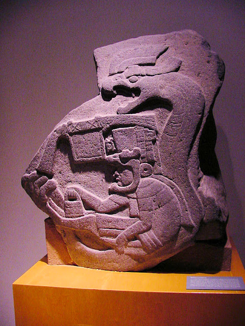 A priest or deity, wearing a large headdress, sits in the coils of a great rattlesnake in this monumental carving (c. 800 BC) on La Venta Stela 19.
