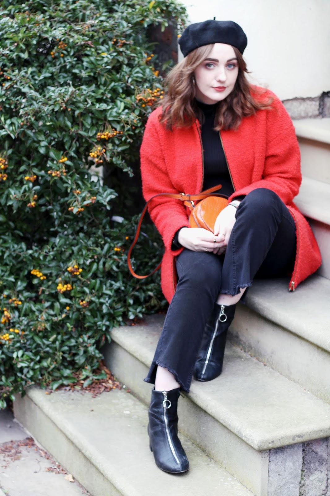 Liverpool fashion blogger wearing black beret, orange coat, orange round bag, black top, black kick flare jeans and black zip up boots