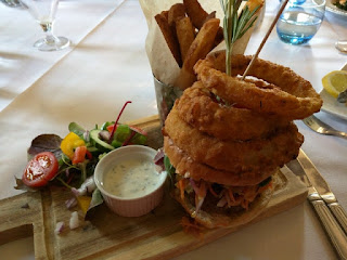 Lamb burger topped with a tower of onion rings, Oswestry, England