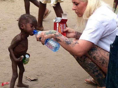 Anja Loven offering water to Nigerian Kid