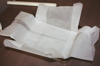 a perspex baking tray with a crossover of baking parchment on a table