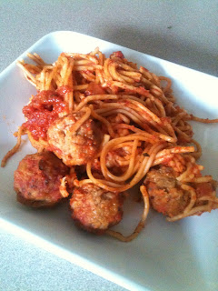 Slow cooked spaghetti and meatballs served on a white plate.
