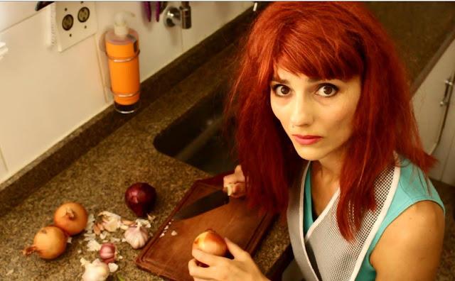 Francine está de peruca ruiva e olha para a câmera. Está cortando cebola e alho em um tábua na pia.