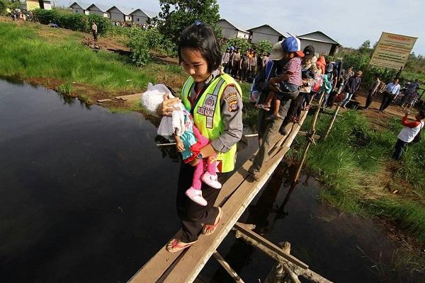 Bripda Novita Elmi Nainggolan Menggendong Balita Melintasi Jembatan Setapak Saat Evakuasi Warga Eks Gafatar
