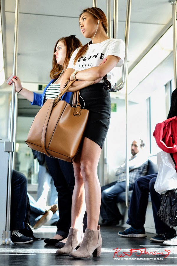 Young Asian woman on Cityrail train wearing black skirt, Céline Paris tee shirt, Suede boots and large brown Céline Paris handbag. Street Fashion Sydney by Kent Johnson.
