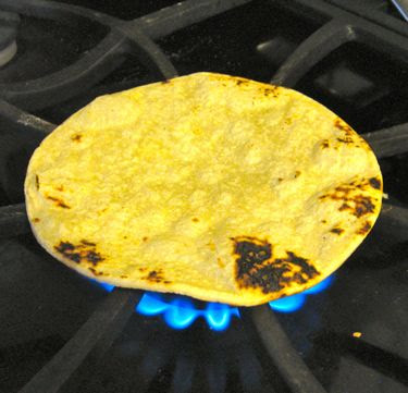 toasting corn tortillas on the gas jet