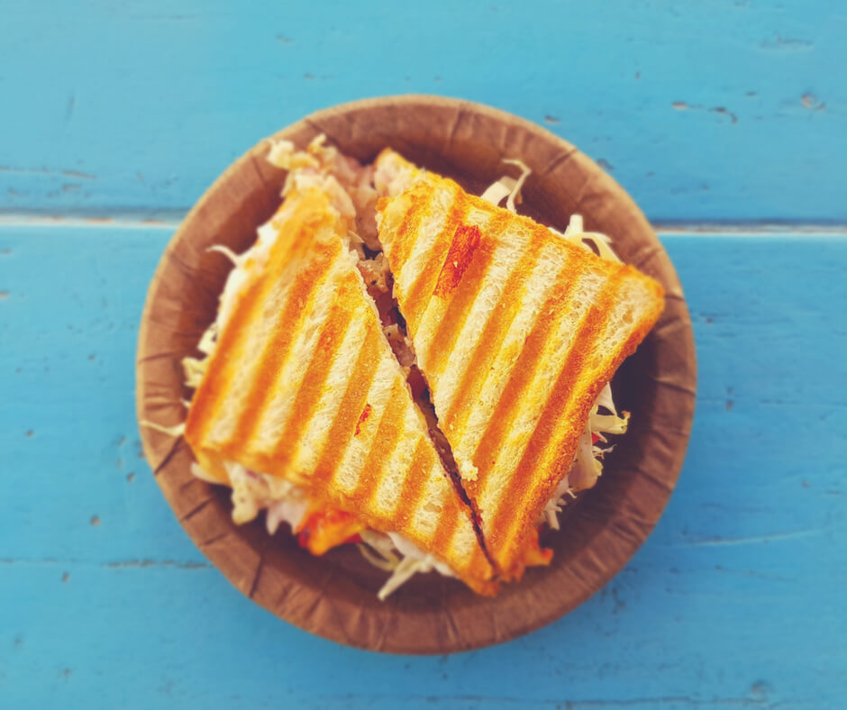 A toasted sandwich on a brown plate - a blue background.