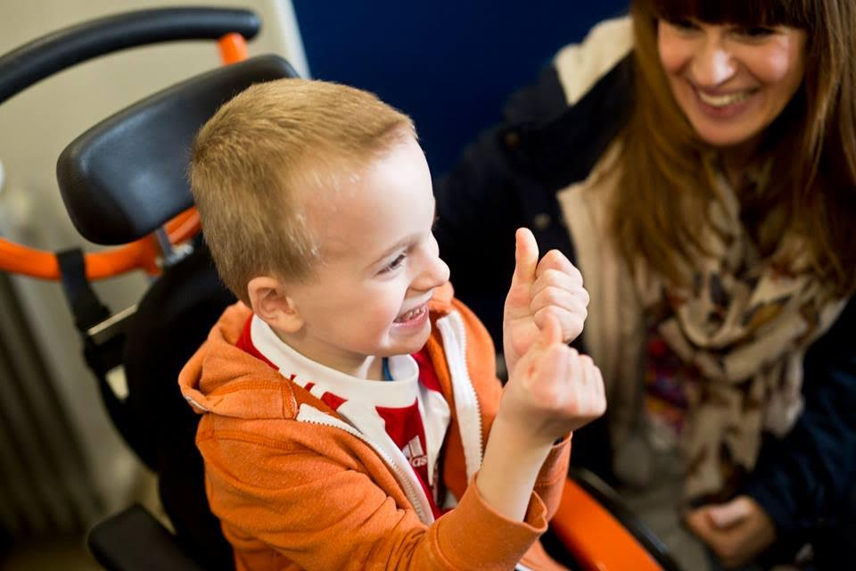 Boy sitting in a wheelchair, wearing a red top and orange hoodie, smiling with his thumbs up.Woman visible in the background is smiling.
