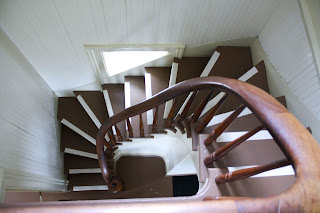 Looking down into a spiral staircase that is rectangular to match the narrow rectangular walls that border it