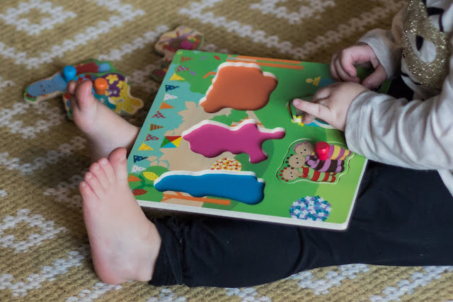 A close up of a child putting a piece in the peg puzzle