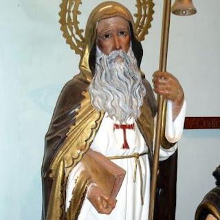 Escultura de san Antonio Abad con un libro en una mano y vara con campana en la otra