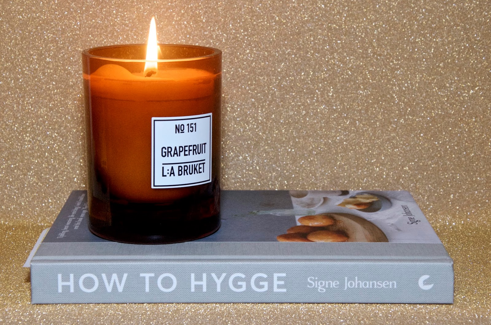 brown glass candle and hygge book