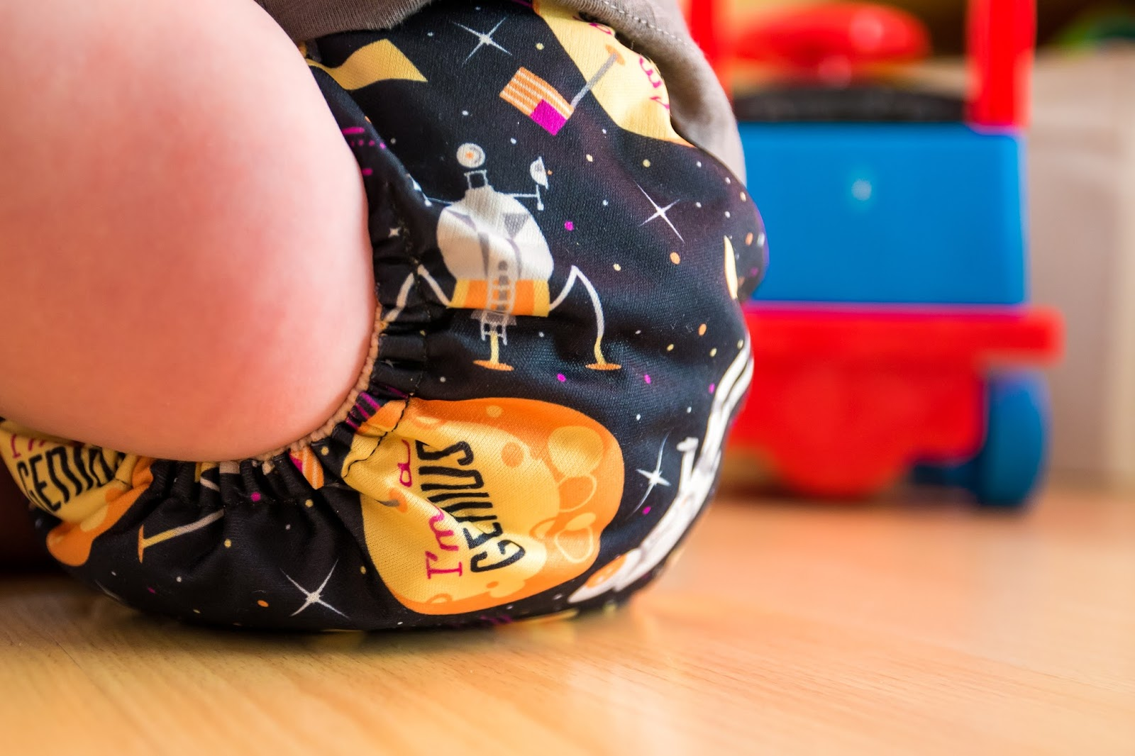 close up of toddler sitting on floor wearing bumgenius cloth nappy with space design