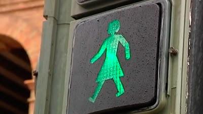 Semáforo con un monigote en forma de mujer con falda