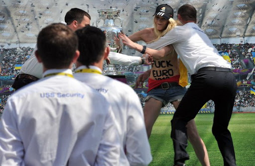 Security tries to stop a female protester as she grabs the European Championship trophy