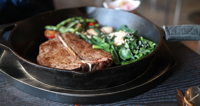 T-Bone Steak and Spinach Cooking in a Cast Iron Skillet
