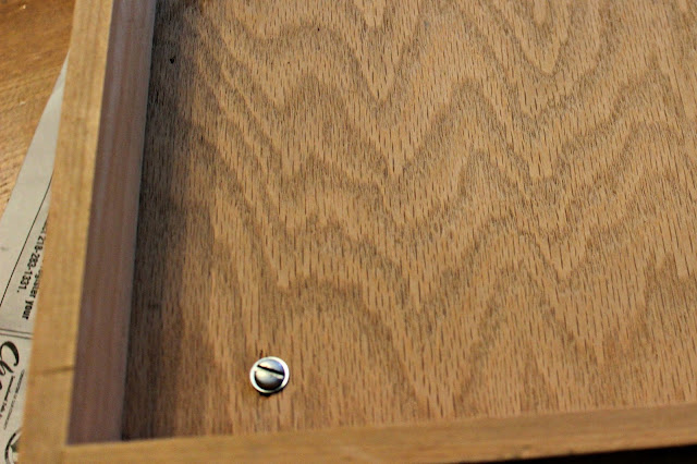 Photo of a screw through the bottom of a drawer into a finial