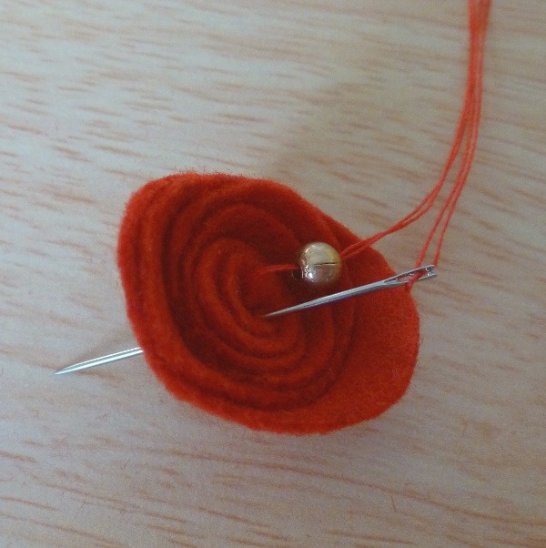Sewing gold color bead into middle of a red felt flower