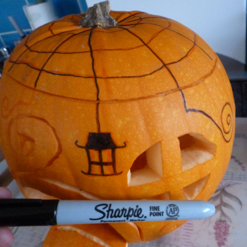 Black pen designs drawing onto pumpkin lid with spider web cobweb