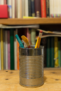 Cramer Imaging's photograph of a can with pencils and a bookshelf demonstrating bokeh