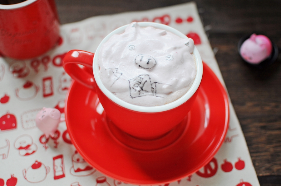 a cream coffee with pig drawing on top