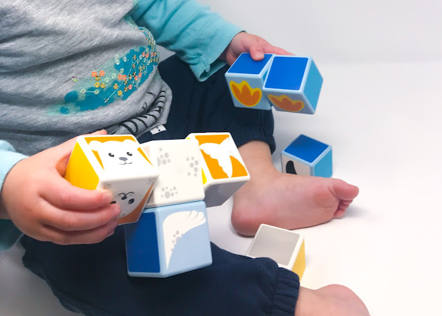 A close up shot of a toddler playing with magnetic cubes with pictures on