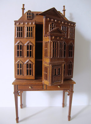 Dolls' house miniature wooden dolls' house mounted on a desk, with the front open to show the shelves inside.