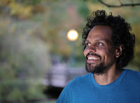Photo of Ross Gay. Trees in the background. He is smiling and wearing a blue shirt.