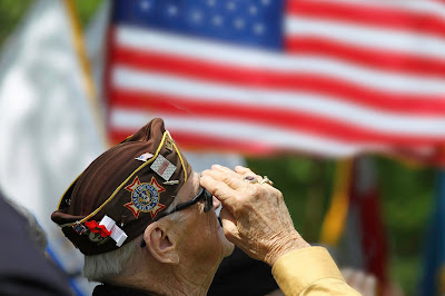 image of an older veteran saluting in front of flags