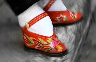 Mujer china mostrando calzado para pies vendados