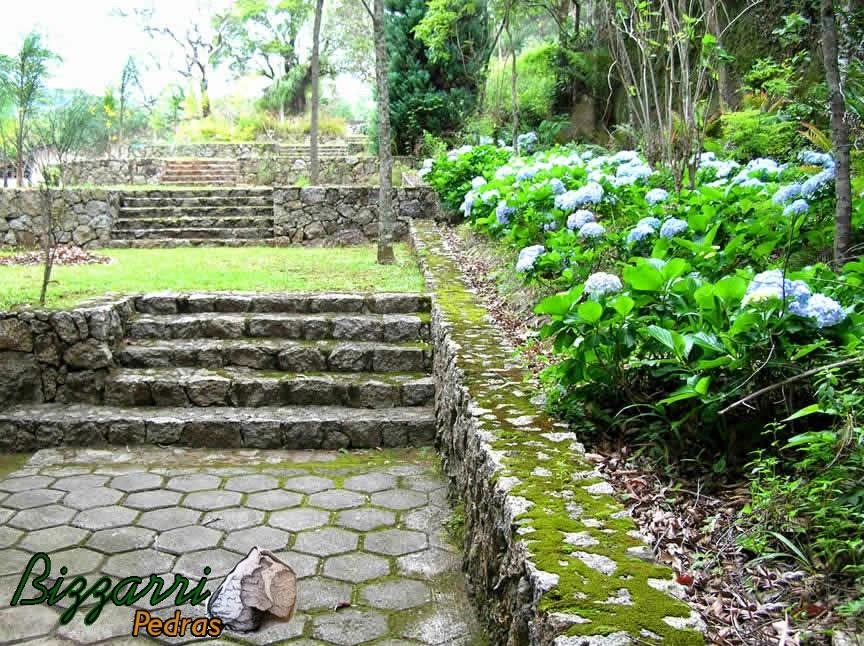 Calçamento com bloquetes de concreto com a escada de pedra rústica com o muro de pedra rústica.