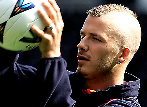 Picture of David Beckham with a Mohawk hairstyle and his scalp shaved while holding a football