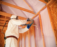 Contractor installing spray foam insulation in a wall
