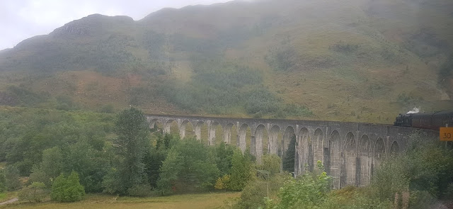 The Glenfinnan Viaduct curving round into green foliage and trees. The impressive stone and brick breaks up the green of the surrounding hills as the black steam train begins to cross it.