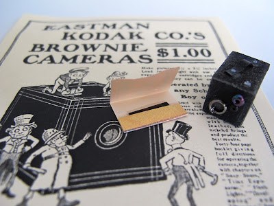 1/12-scale vintage box brownie camera and photo packet, on a full-sized advertisement for the camera.