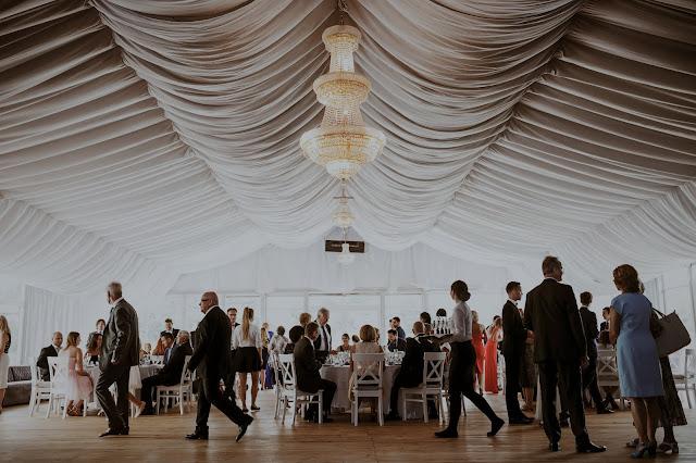 Efektowne wesele w namiocie z sufitem pokrytym drapowanym materiałem i eleganckimi żyrandolami. Lightsome Studio