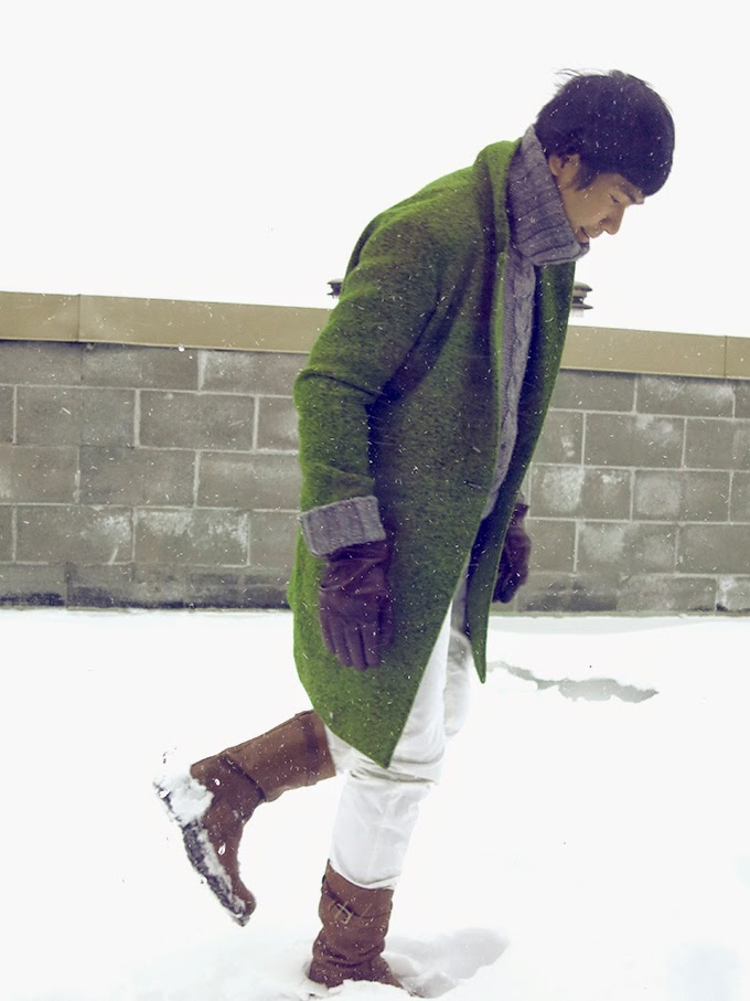 Ben walking in the winter wind and white snow, with Sergio Rossi brown leather boots, wearing unisex apple green wool coat