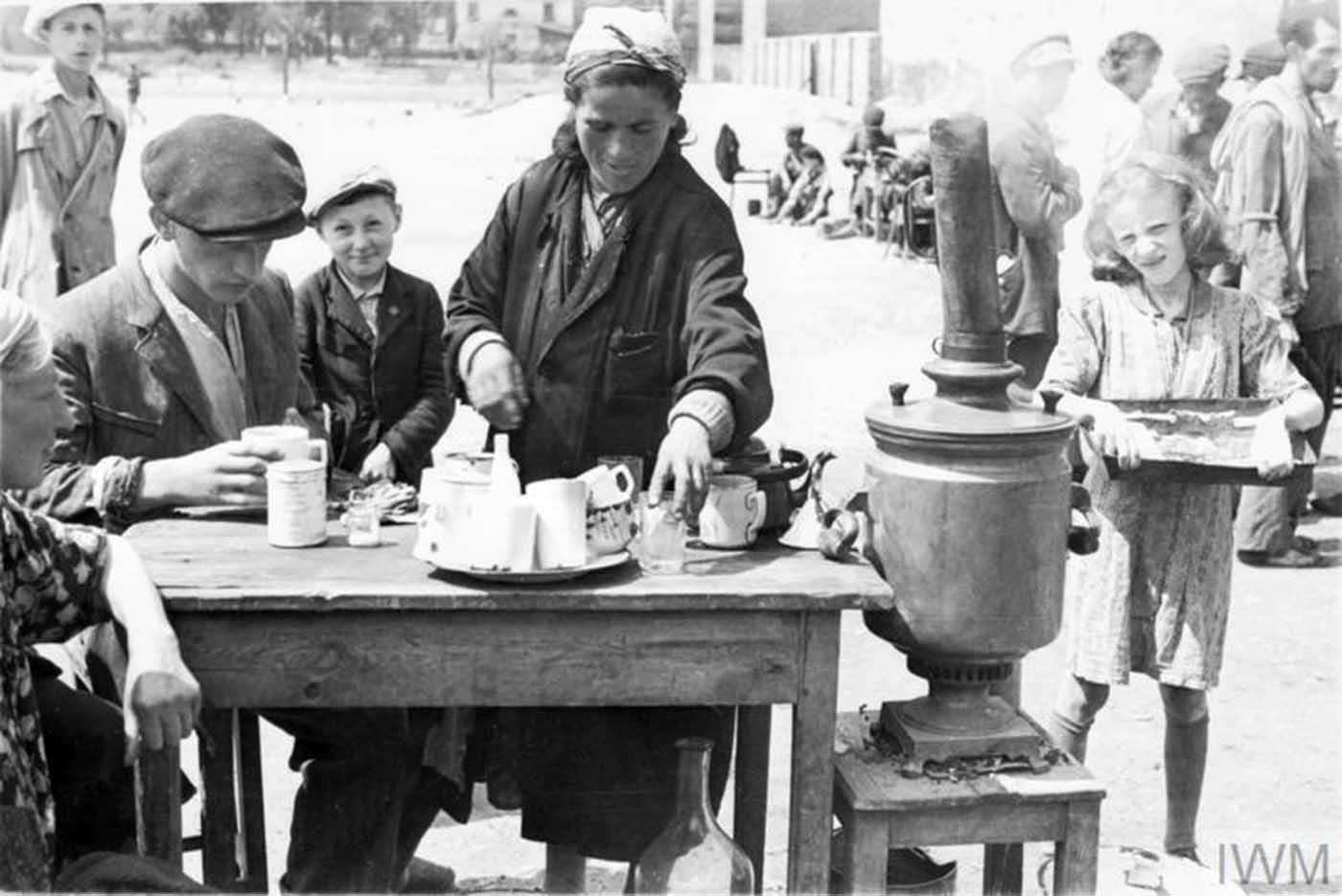 A female tea seller serving hot drinks to customers in a makeshift cafe in a street market in the ghetto.