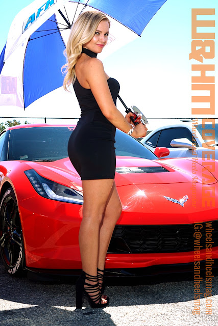 blonde model Lisa Lee Marie in a mini black dress, holding umbrella, in front of a red corvette