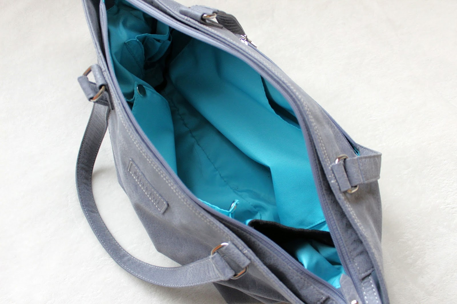 Large grey handbag open revealing a turquoise interior, some pockets are visible.
