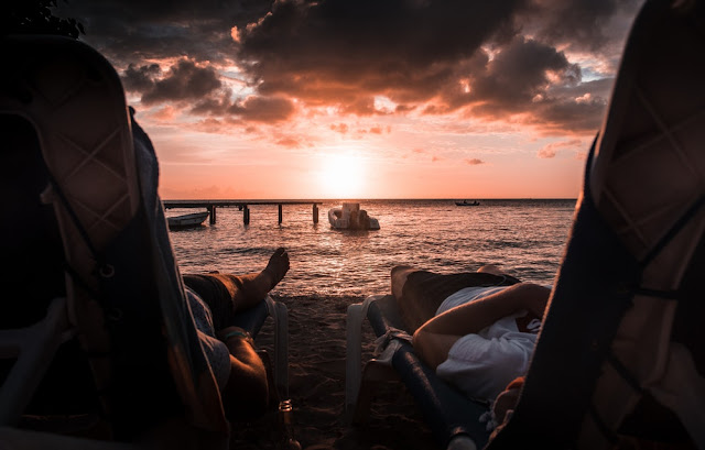 people sitting on sun loungers as the sun sets out at sea