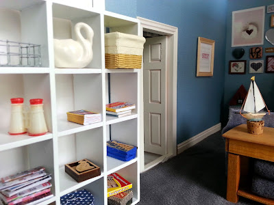 One-twelfth scale modern miniature lounge cube bookcase with various games and puzzles on the shelves along with a stack of magazines and a pair of binoculars.