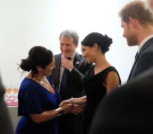 Meghan Markle Wore Black Halo Jackie Belted Dress and Gucci clutch and Aquazurra ankle-strap heels. Prince Harry, Foreign Secretary Boris Johnson