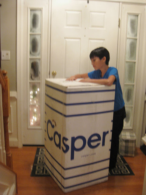 Boy holding a big Casper box on the front door.