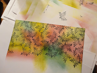 Coloured ink background stamped with black holly images